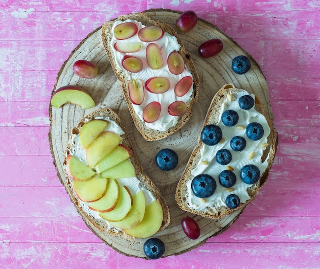 Healthy open sandwiches with fruits, peach grapes blueberries and soft cheese on pink wooden background,  top view,  flat lay