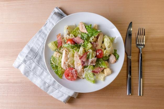 Здоровый органический салат цезарь с курицей. свежий салат цезарь с жареной курицей в деревянной тарелке.