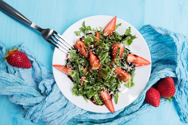 Healthy organic diet salad with arugula, strawberries and sesame with balsamic glaze