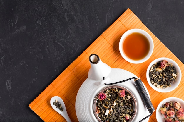 Healthy organic dried tea herb and teapot on orange placemat over black background