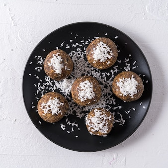 Healthy organic energy balls made with dates, prunes, raisins, peanut, with coconut shavings, in black plate on white
