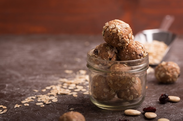 Healthy organic energy granola bolls with nuts, cacao, oats and raisins - vegetarian sweet bites without sugar. dark background