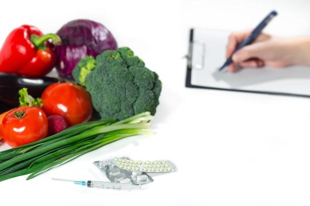 健康的な有機食品または医薬品の概念。ダイエット計画、新鮮な野菜の組成、白い背景で隔離の薬や注射器を書く女性の手