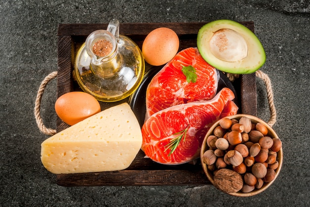 Healthy organic food. products with healthy fats. omega 3, omega 6. ingredients and products: trout (salmon), olive oil, avocado, nuts, cheese, eggs. on dark stone table. copyspace top view