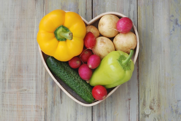 Здоровые натуральные продукты, овощи в деревянной коробке формы сердца.