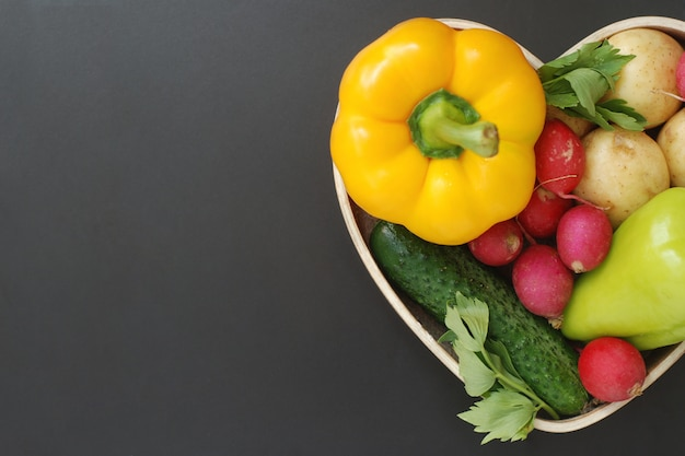 Healthy organic foods, vegetables in wooden heart shape box.