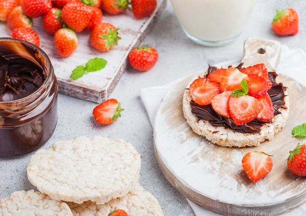 Healthy organic rice cakes with chocolate butter and fresh strawberries on wooden board and glass of milk