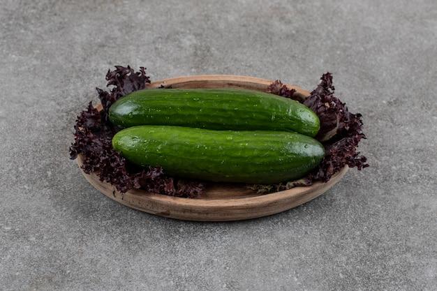Cetrioli maturi organici sani in piatto di legno.