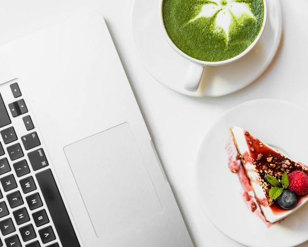 Healthy organic summer dessert; matcha tea cup near the laptop on white desk