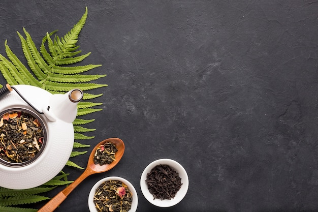 Healthy organic tea with dry herb and fern leaves on black surface