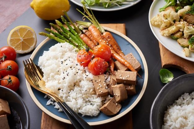Здоровый органический тофу и миска будды риса с овощами.