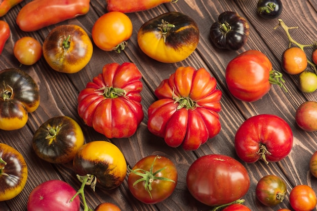 木製の背景に健康的な有機トマト。素朴な木製の背景にトマトの盛り合わせ。