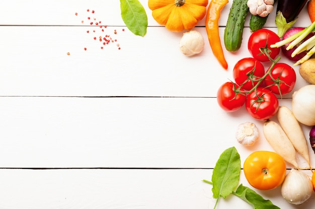 Healthy organic vegetables composition on white wooden table with copy space. top view.
