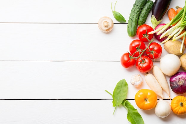 Healthy organic vegetables composition on white wooden table with copy space.