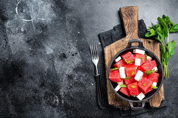フェタチーズとヘルシーなオーガニックスイカのサラダ。黒の背景。上面図。スペースをコピーします。
