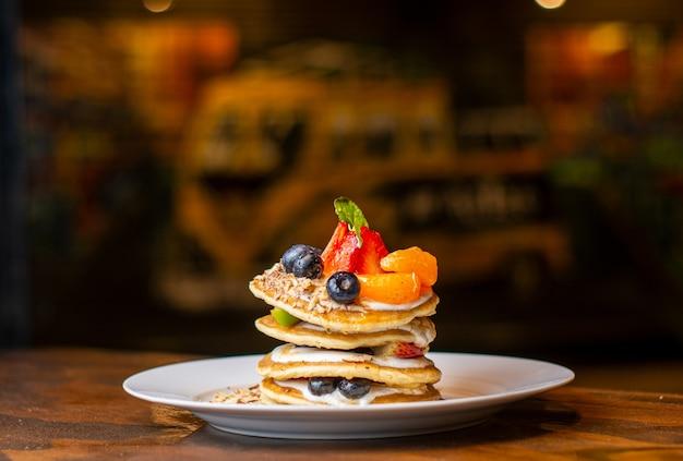 白いプレートにフルーツシリアルと蜂蜜と背景をぼかす健康的なパンケーキ
