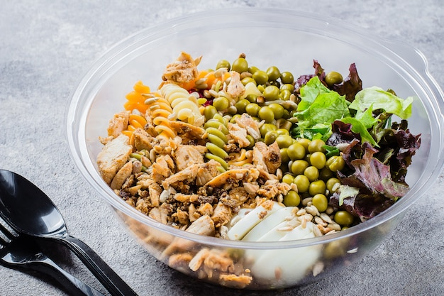 Healthy pasta bowl chicken, pasta fusilli, mix greens, green peas a in plastic bowl.