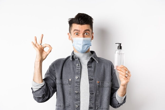健康な人とcovid-19コンセプト。良い手指消毒剤のボトルを保持している医療マスクの興奮した男は、大丈夫な兆候を示し、白い背景に立って、消毒剤をお勧めします。