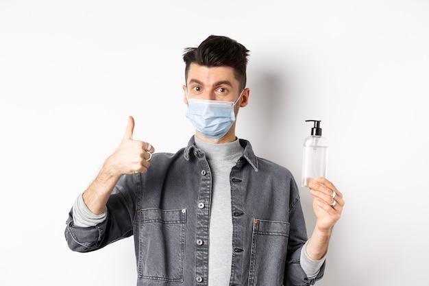 健康な人とcovid-19コンセプト。良い手指消毒剤のボトルを保持している滅菌医療マスクの興奮した男は、親指を立てて、白い背景に立って、消毒剤をお勧めします。