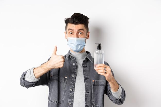 건강한 사람과 covid-19 개념. 좋은 손 소독제의 병을 들고 멸균 의료 마스크에 흥분된 남자, 엄지 손가락을 표시하고, 방부제를 권장하고, 흰색 배경에 서 있습니다.