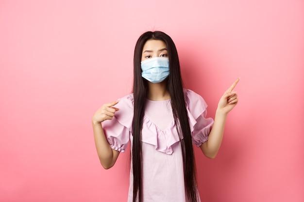 Здоровые люди и концепция пандемии covid-19. скучно азиатская женщина в медицинской маске, указывающая вправо, показывая логотип, недовольная стоя на розовом фоне.