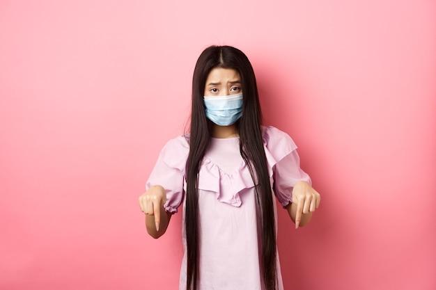 健康な人々とcovid-19パンデミックの概念。ピンクの背景に立って、怒って眉をひそめ、指を下に向けて悲しいアジアの女性。