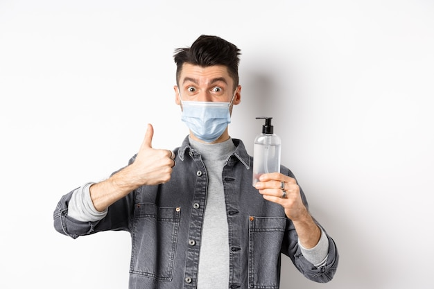 Healthy people and covid-19 concept. excited man in sterile medical mask holding bottle of good hand sanitizer, show thumb up, recommend antiseptic, standing against white background.
