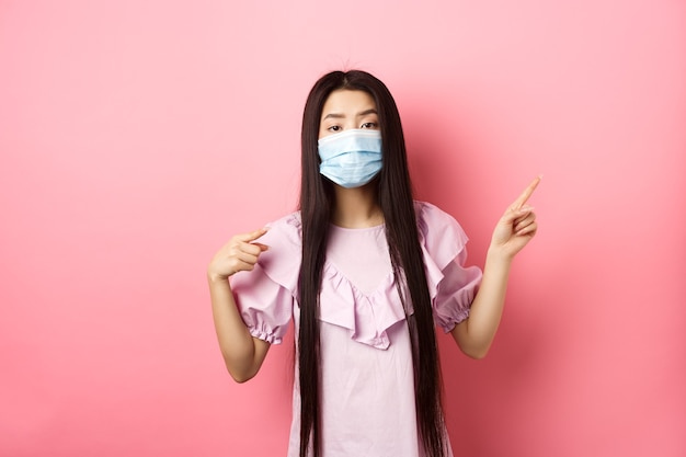 Healthy people and covid-19 pandemic concept. bored asian woman in medical mask pointing right, showing logo, standing unamused on pink background.