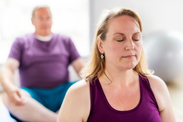 Здоровые люди делают позу сукхасаны на уроке йоги