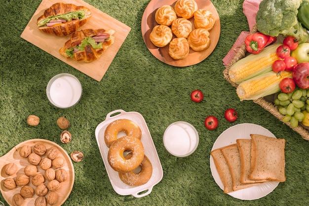 Здоровый пикник для летних каникул со свежеиспеченными круассанами, свежими фруктами и фруктовым салатом, бутербродами и стаканом освежающего апельсинового сока, выложенными на красно-белой клетчатой ткани и корзине.