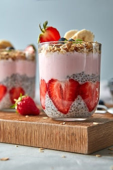 Healthy pink smoothie in glasses with natural fruits strawberry, banana, blueberry