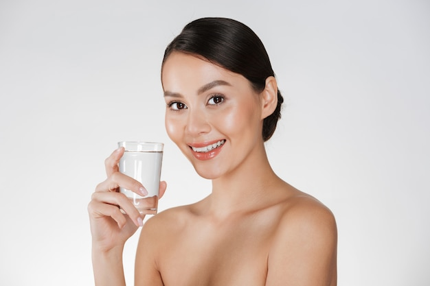 Healthy portrait of young happy woman with hair in bun drinking still water from transparent glass, isolated over white