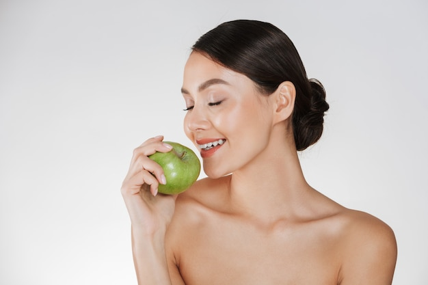 Healthy portrait of young woman with soft fresh skin enjoying green juicy apple, isolated over white