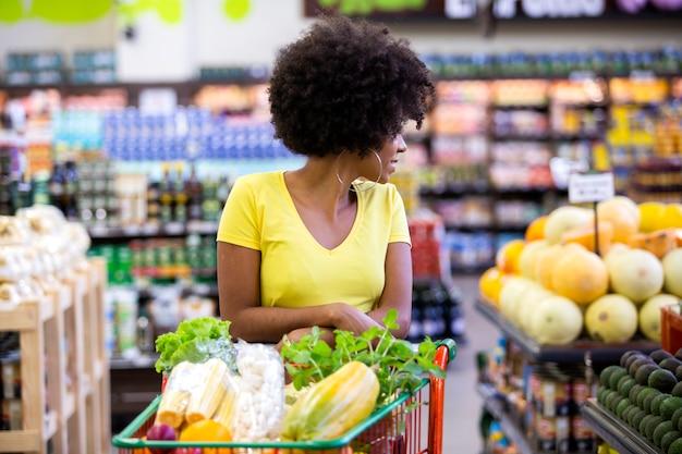 Здоровая положительная счастливая африканская женщина, держащая корзину, полную фруктов и овощей.