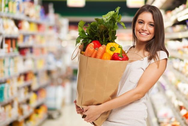 果物や野菜でいっぱいの紙のショッピングバッグを持って健康的な肯定的な幸せな女性