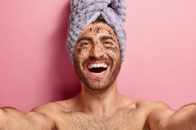 Healthy positive man makes selfie, applies coffee scrub on face skin, has cleansing procedures, poses topless against pink background with towel on head. cosmetology