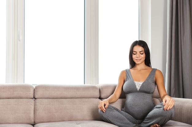 Здоровая беременная женщина в помещении дома, сидя на диване для медитации.