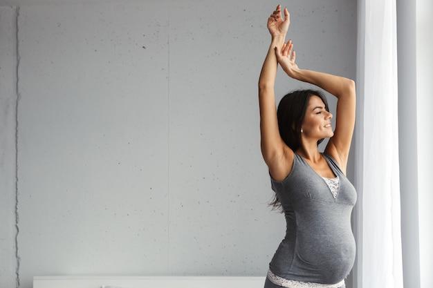 Здоровая беременная женщина в помещении дома на растяжку.