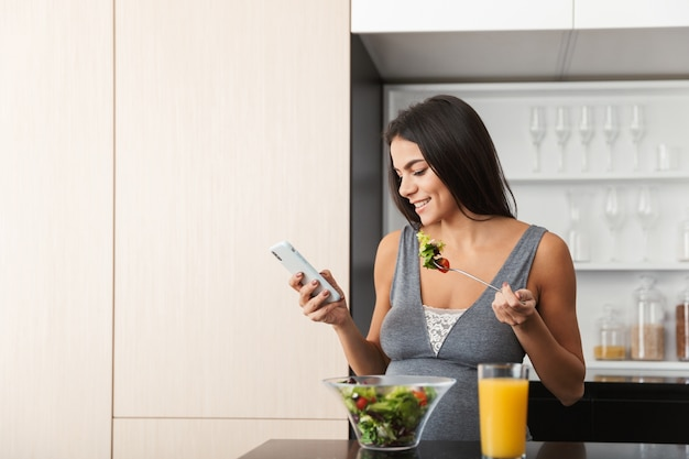 Healthy pregnant woman indoors at home at the kitchen using mobile phone eat salad.