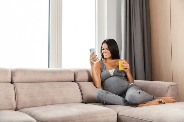 Healthy pregnant woman indoors at home sitting on sofa using mobile phone drinking juice.