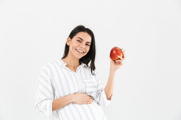 Здоровая беременная женщина с большим животом улыбается и держит в руке яблоко, изолированное над белой стеной