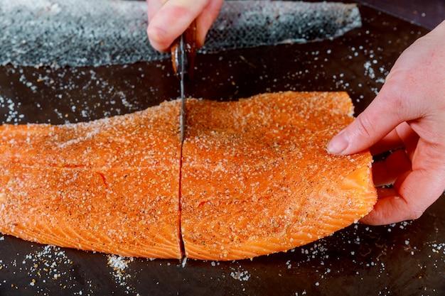 Healthy preparation chef is cuting salmon