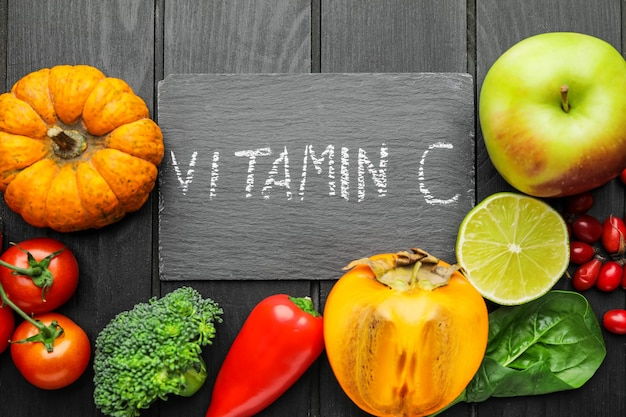 Healthy products rich in vitamin c on dark wooden