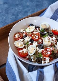 キノア、いくつかの野菜、木製のトレイ上の白いボウルに小さな卵の健康的なプロテインサラダ。コピースペース