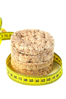 Healthy puffed corn galettes with measuring tape on white background.
