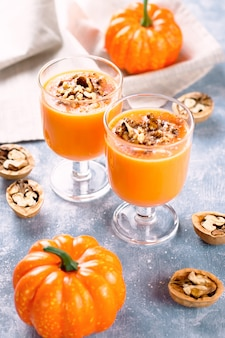 Healthy pumpkin smoothie with walnuts and cinnamon in glasses