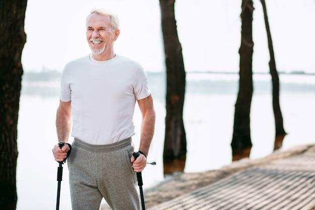 Здоровая спортивная ходьба. веселый зрелый мужчина практикует спортивную ходьбу в парке, смеясь