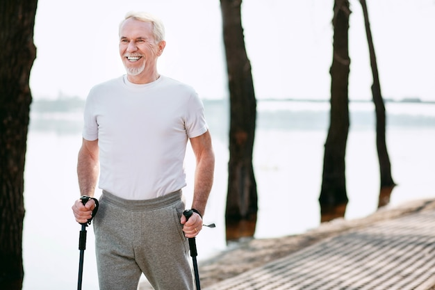 Healthy race walking. jovial mature man practicing race walking in park while laughing