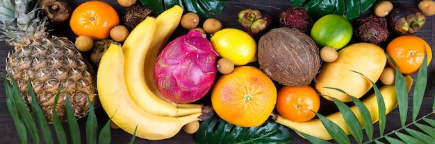 Healthy rainbow tropical fruits banner with palm leaves on blue wooden table