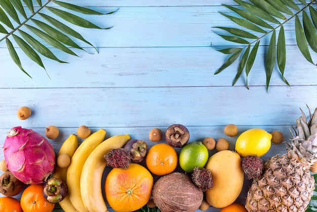 Healthy rainbow tropical fruits frame with palm leaves on blue wooden table